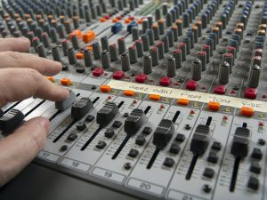 Working on a recording studio mixing board